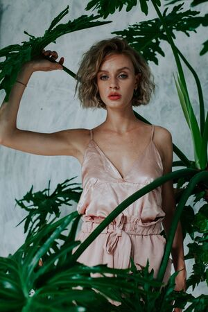Portrait of a beautiful fashionable blonde woman with green leaves of the plant