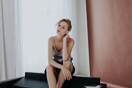 portrait of a beautiful fashionable woman on a black office sofa