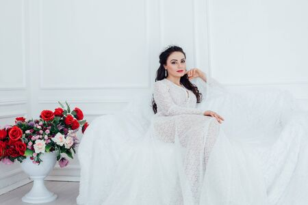 the bride in a wedding dress with a Crown sitting on a white sofa 版權商用圖片
