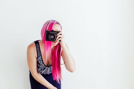 photographer girl with pink hair on a photo shoot with a camera 版權商用圖片 - 134011773