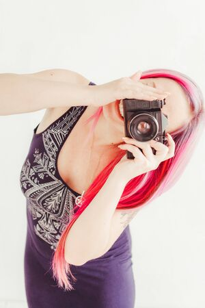 photographer girl with pink hair on a photo shoot with a camera 版權商用圖片 - 134011776