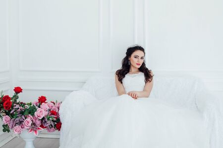 bride in a wedding dress and a crown sits in the white hall 版權商用圖片