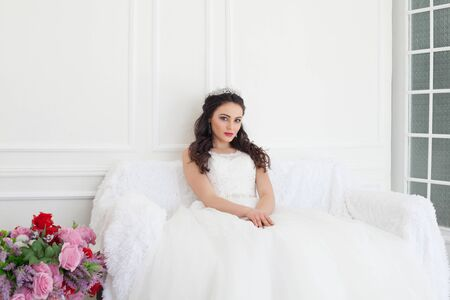 bride in a wedding dress and a crown sits in the white hall Banque d'images
