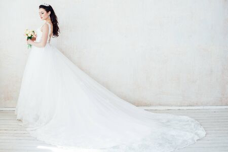 Princess Bride in a wedding dress standing in a room of vintage