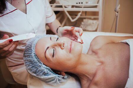 Cosmetology doctor makes woman treatments facial massage 版權商用圖片