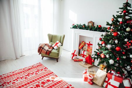 Christmas tree with gifts in the interior of the white room decor for the new year