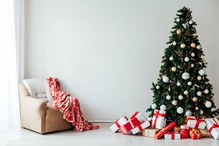 Christmas tree with gifts Of December decor in the interior of the white room as a background