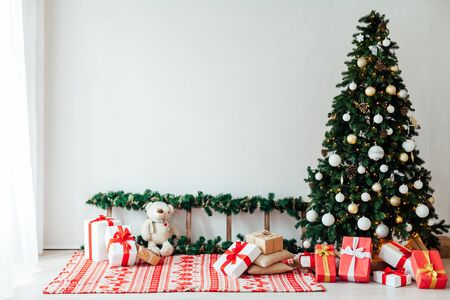 Christmas tree with gifts decor in the interior of the white room as a background