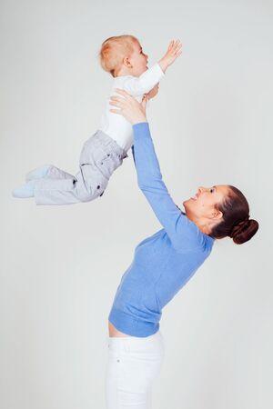 mom raises her son hands up boy