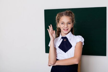 Girl school study stands at the green board in the classroom Foto de archivo