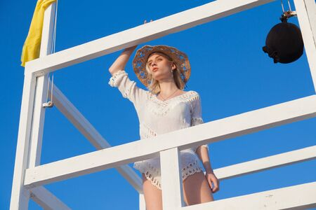 Beautiful fashionable female blonde lifeguard on the beach by the ocean Stock Photo