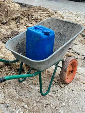 wheelbarrow with blue is on the construction site of the house 스톡 콘텐츠