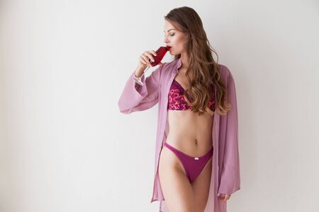 portrait of a beautiful fashionable woman in lingerie with a glass of wine