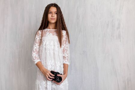 portrait of a beautiful fashionable girl with a camera in white pink clothes Zdjęcie Seryjne