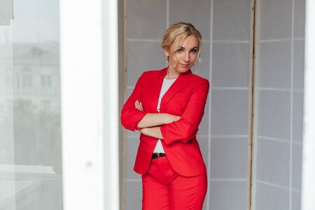 Beautiful blonde woman in red business suit in business office