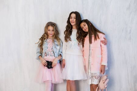 Portrait of three beautiful fashionable girlfriend girls with a camera in white pink clothes