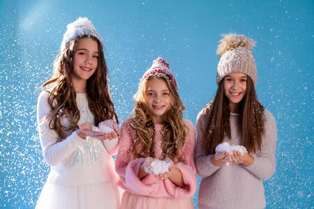 Three beautiful fashionable girl girlfriends in a winter snow cap