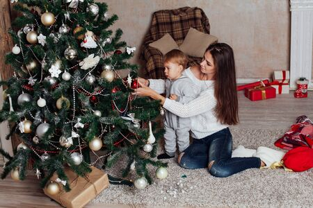 mother and little boy at Christmas tree with gifts 1