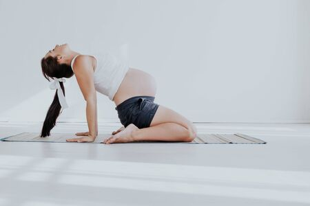 a pregnant woman is engaged in gymnastics and yoga