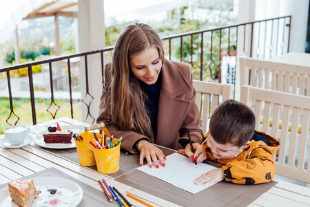 mom helps son to draw drawing colored pencils