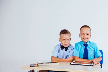 the two boys are looking at Internet Tablet school
