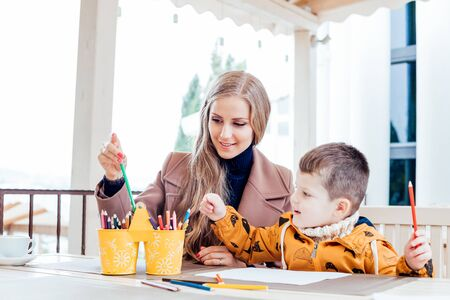 mother and son in the restaurant painted pencils before eating Zdjęcie Seryjne