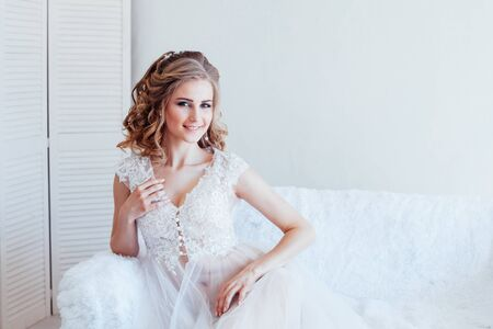 beautiful bride sitting on a white couch in lingerie Stock Photo