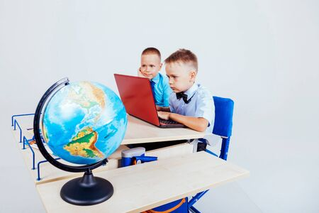 two boys sit at the computer training school