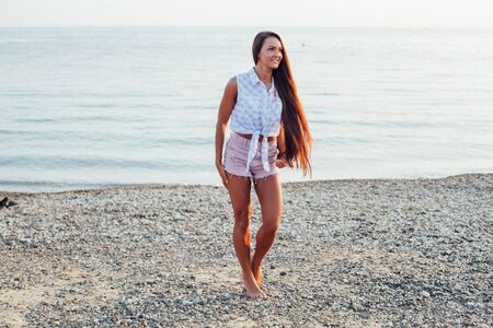 beautiful woman with long hair walks on the beach by the sea