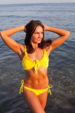 Beautiful woman with long hair in a yellow swimsuit walks on the beach by the sea Stock Photo