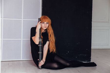 beautiful woman anime cosplayer with red hair with Japanese sword