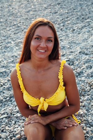 Beautiful woman with long hair in a yellow swimsuit walks on the beach by the sea Stock fotó
