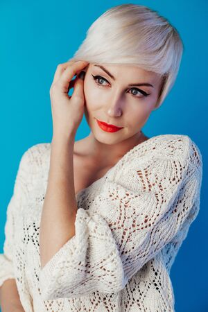 Portrait of blonde with short hair on a blue background