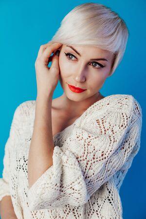 Retrato de rubia con pelo corto sobre un fondo azul.