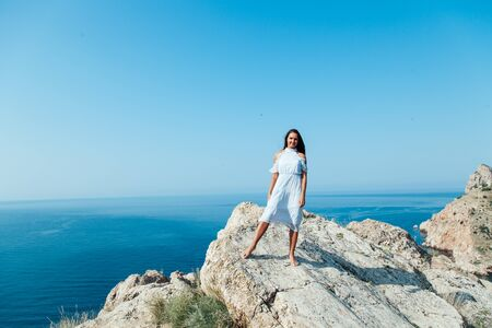 Beautiful woman in a dress with long hair travels a beautiful sea landscape