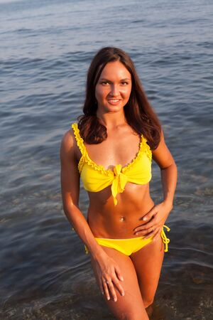 Beautiful woman with long hair in a yellow swimsuit walks on the beach by the sea 스톡 콘텐츠