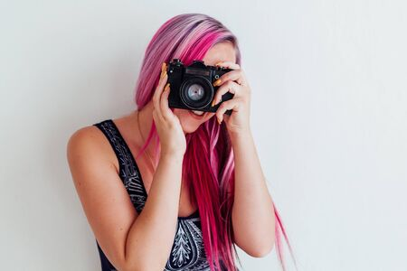 girl with pink hair photographs camera photo