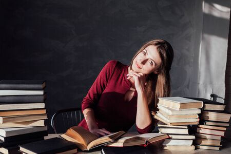 the girl sitting at the table reading a lot of books