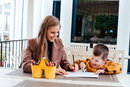 mom and young boy draw colored pencils