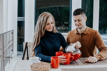 husband with wife on holiday drink hot coffee and tea