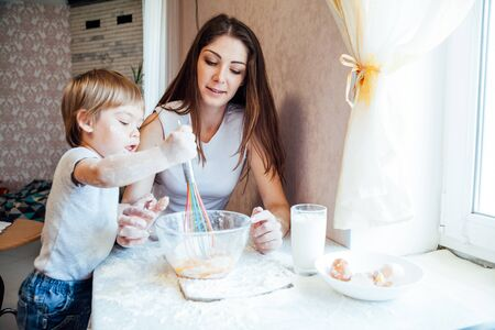mother and young son prepare pie in the kitchen