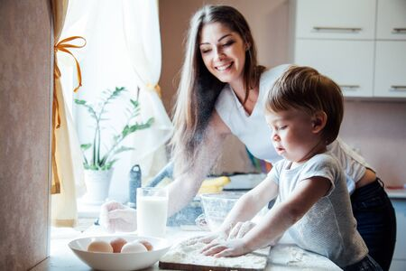 mother and young son prepare a cake in the kitchen