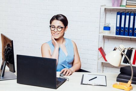 business girl sits in an Office behind a desk with a computer