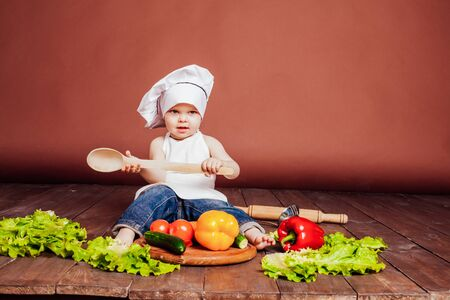 the boy chef with a wooden spoon, carrots, peppers, tomatoes, lettuce, cucumber Zdjęcie Seryjne