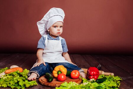 little boy Cook carrots, peppers, tomatoes, lettuce,