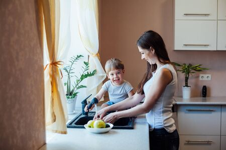 kitchen mom son wash fruits and vegetables Zdjęcie Seryjne