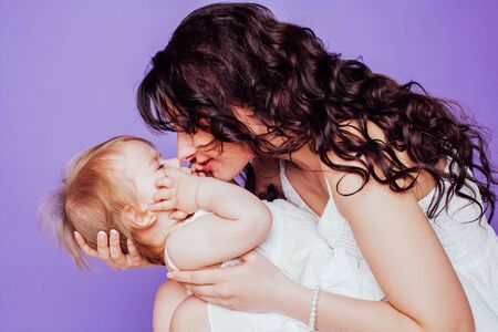 mother and little daughter play smile on purple background