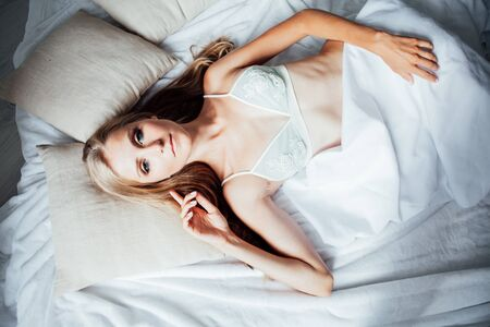 Beautiful blonde woman wakes up in the morning in the bedroom