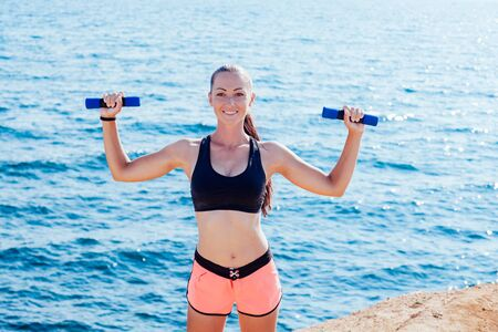 girl Sports Fitness on the beach by the sea