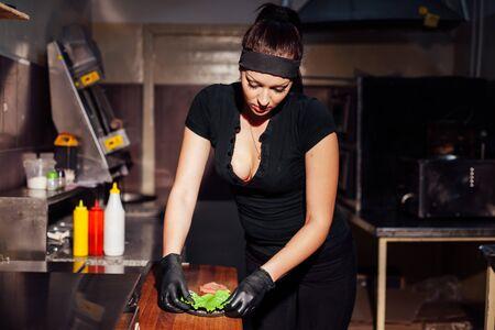 beautiful girl Cook prepares the kitchen Burger